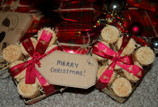 Two small, open boxes of Waxling firelighters wrapped in red ribbon with a Merry Christmas gift tag