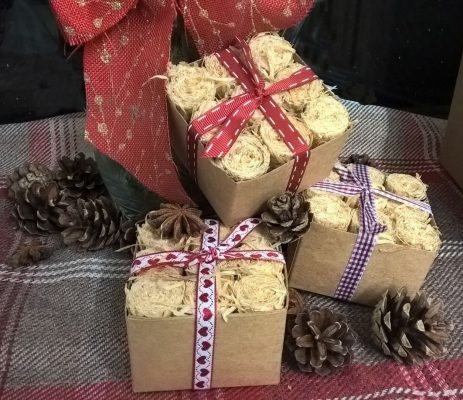 Three small gift boxes of Waxling firelights, wrapped in red and white riboon, with pine cones and star anise decorations
