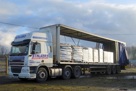 An HGV with curtain sides open, showing a number of pallets of wood fuel ready to unload